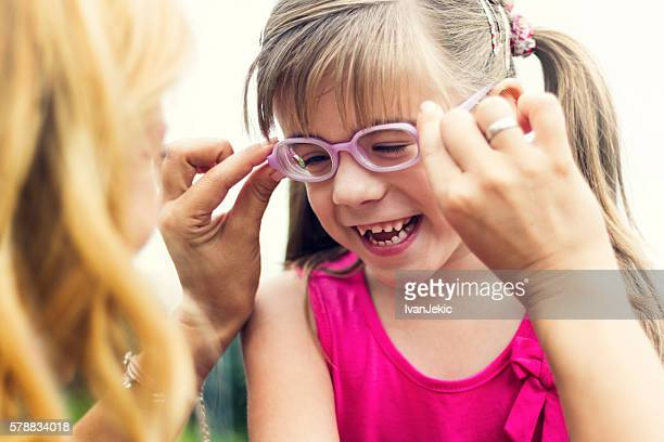 Mother putting eyeglasses on her daughter
