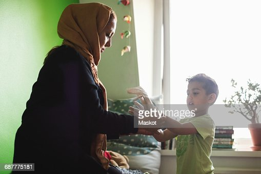 Mother putting gloves on sons hand in bedroom