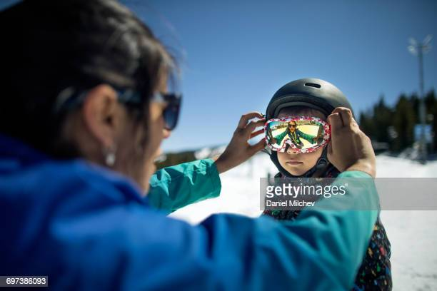 Mother putting goggles on her young son.