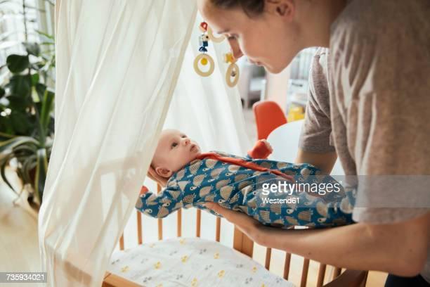 Mother putting her newborn baby boy into crib