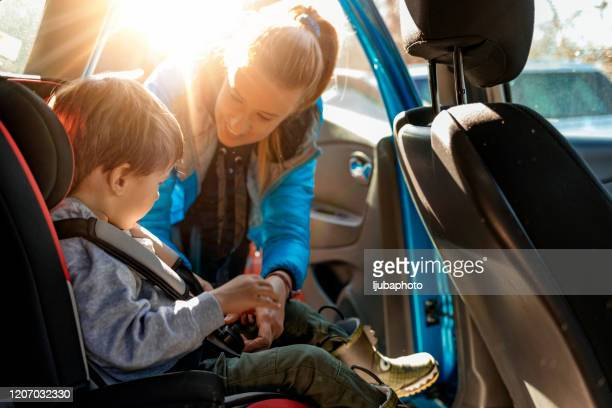 mother putting her son in a car with his car safety seat - family with one child stock pictures, royalty-free photos & images