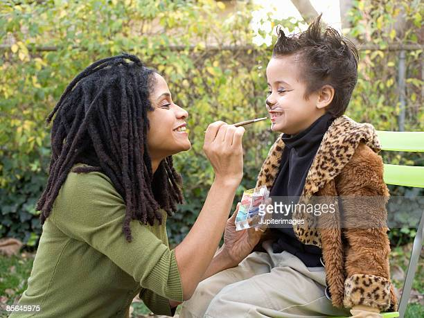 Mother putting makeup on son