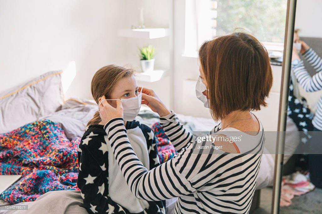 Mother putting mask on daughter : Stock Photo