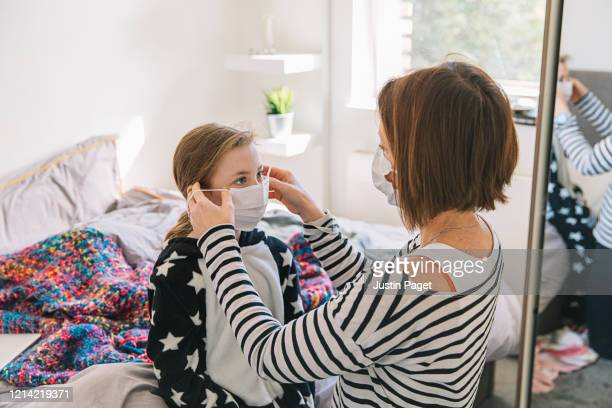 mother putting mask on daughter - pandemic illness stock pictures, royalty-free photos & images