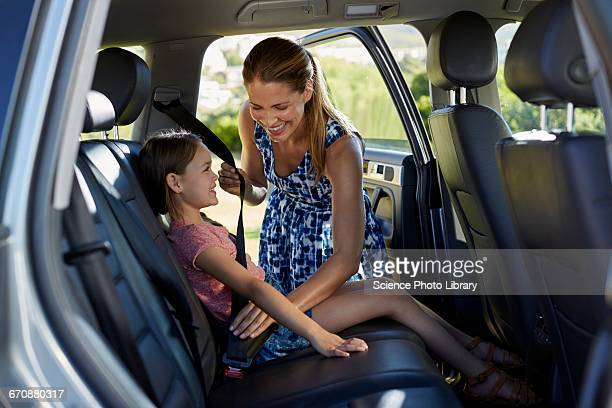 Mother putting on daughters seat belt