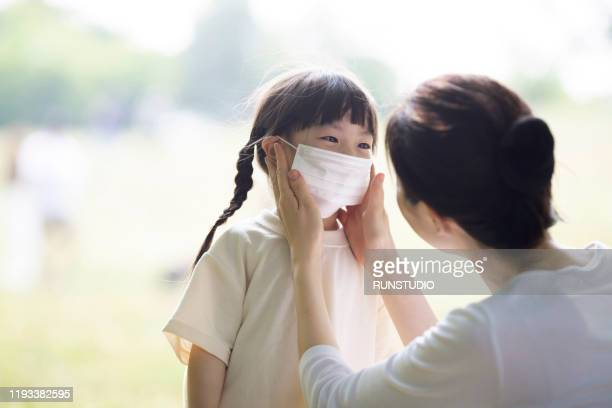 mother putting on pollution mask to girl - 医療とヘルスケア ストックフォトと画像