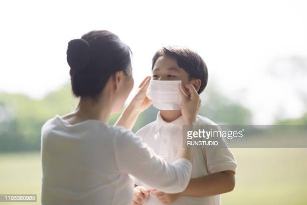 mother putting on pollution mask to son - 医療とヘルスケア ストックフォトと画像