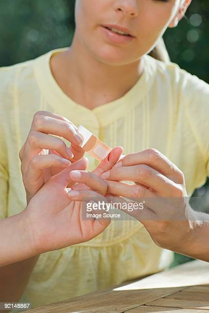 mother putting plaster on childs finger - finger injury stock pictures, royalty-free photos & images