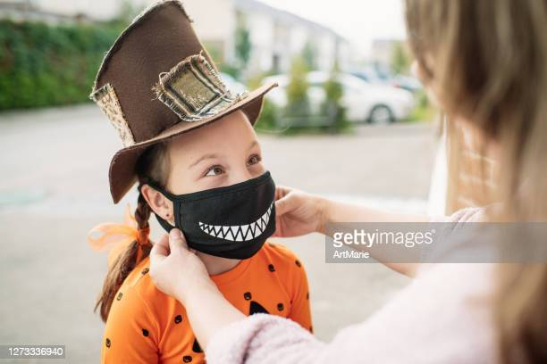 mother putting protective face mask on her child during covid-19 pandemic on halloween - tradition stock pictures, royalty-free photos & images