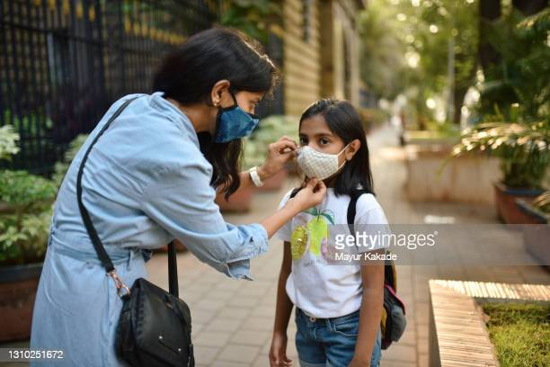 mother putting protective face mask on her daughter's face - マハラシュトラ州 ストックフォトと画像