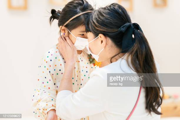 mother putting protective mask on her daughter`s face - surgical mask stock pictures, royalty-free photos & images