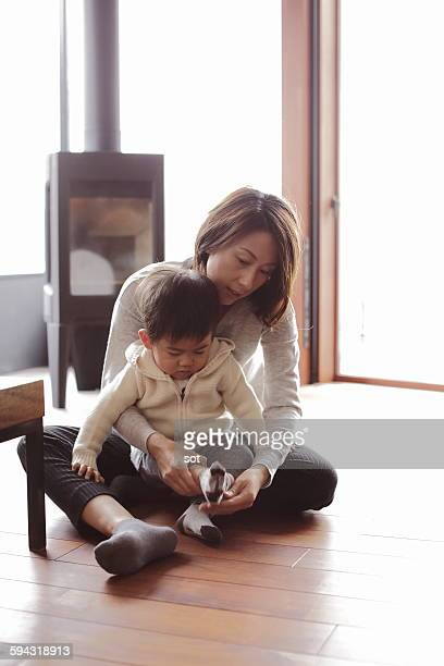 Mother putting socks on baby boy in living room