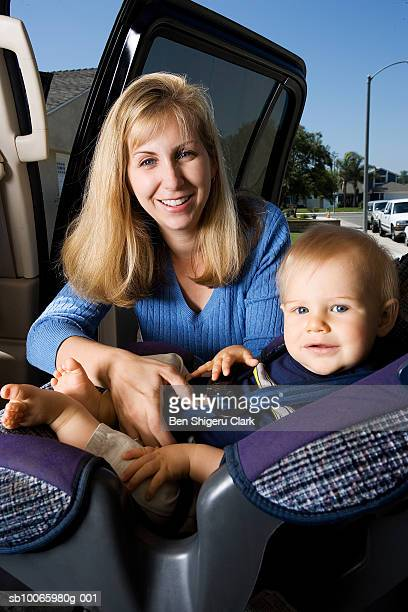 Mother putting son (9-12 months) into car seat, portrait