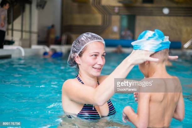 Mother putting son swimming cap in the pool
