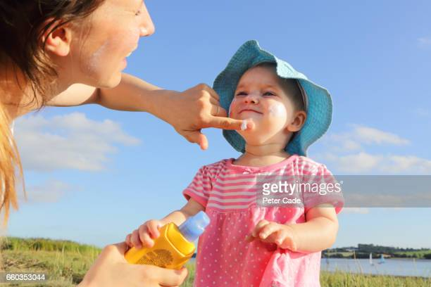 mother putting sun cream on toddler girl - protection stock pictures, royalty-free photos & images