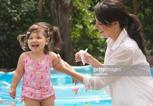 Mutter und Tochter setzen Sonnenschutz auf baby