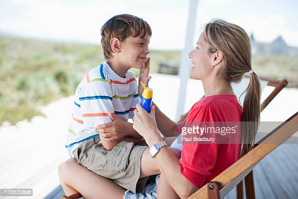 mother putting sunscreen on boy - sunscreen stock photos and pictures