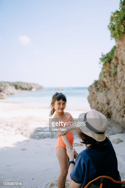 mother putting sunscreen on her daughter at beach - ippei naoi stock pictures, royalty-free photos & images