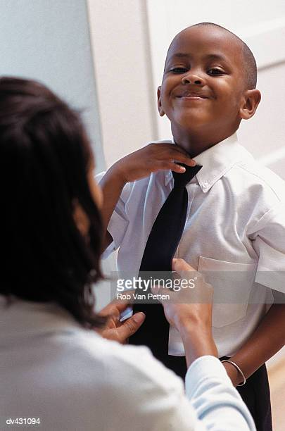 Mother putting tie on son
