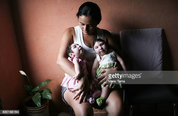 Mother Raquel holds her twin daughters Eloa and Eloisa, 8 months old and both born with microcephaly, while posing on December 16, 2016 in Areia,...