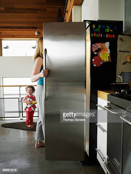 Mother reaching in refrigerator in home