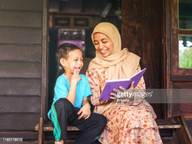 mother read book with son - ibnjaafar stock photos and pictures