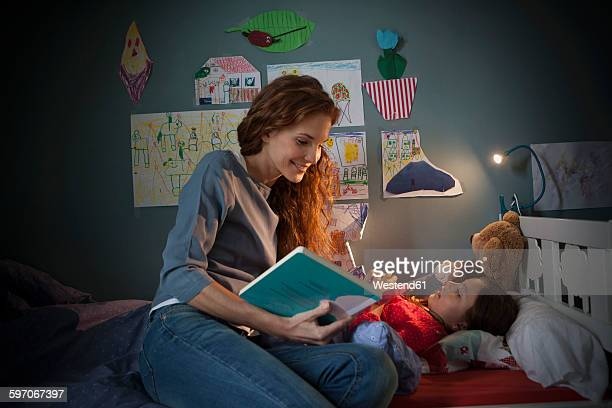 mother reading a bedtime story for her little daughter - family with one child stock pictures, royalty-free photos & images