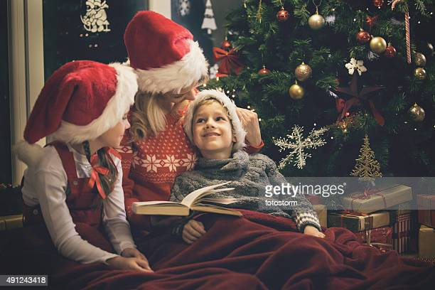 Mother reading a book to children during Christmas holidays
