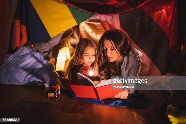 Mother reading a book to her daughter at night