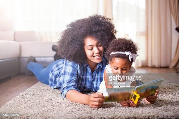 Mutter beim Buchlesen zu Ihrer Tochter auf dem Teppich