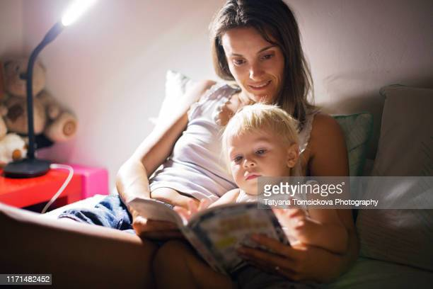 mother, reading a book to her toddler boy at home at night, night stand lamp turned on, mom and baby hugging - lire photos et images de collection