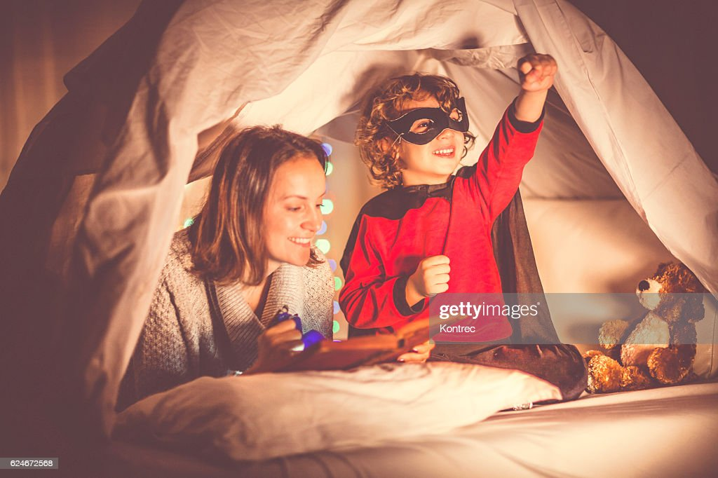 Mother reading a story to her son at bedtime : Stock Photo