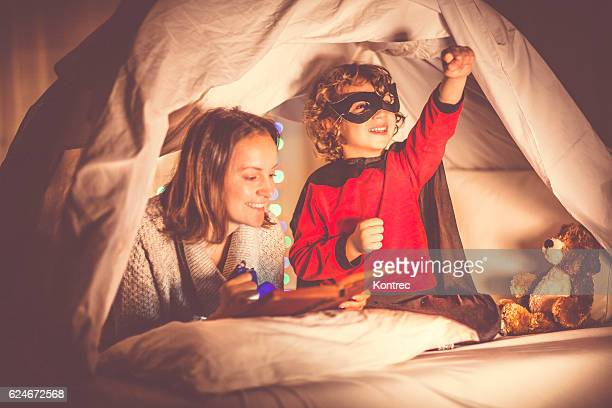 mother reading a story to her son at bedtime - fairytale stock pictures, royalty-free photos & images