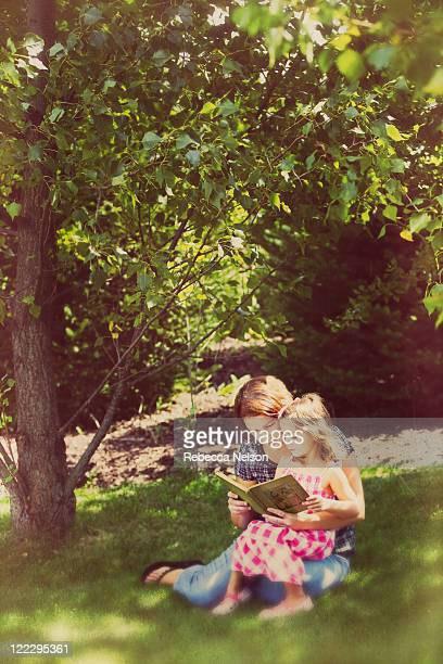 mother reading and daughter on her lap - rebecca nelson stock pictures, royalty-free photos & images