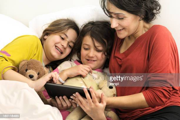 Mother reading bedtime e-story to daughters