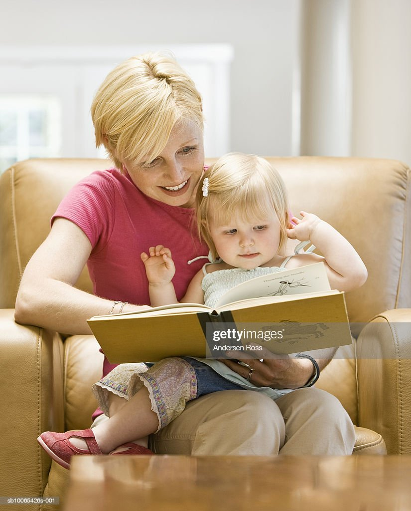 Mother reading book to baby daughter (9-12 months) : Foto stock
