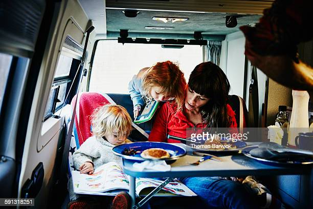 Mother reading book to children in camper van