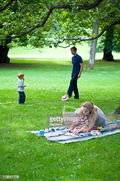 Mother reading book to daughter and father playing soccer with son in the park