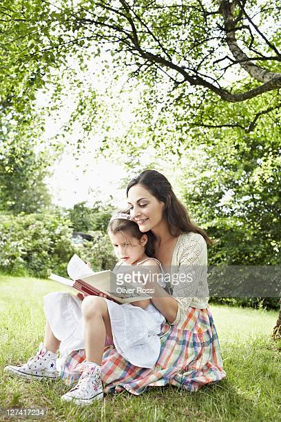 mother reading book to young girl