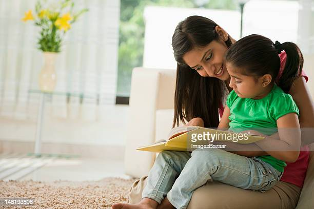 Mother reading book with daughter (6-7)