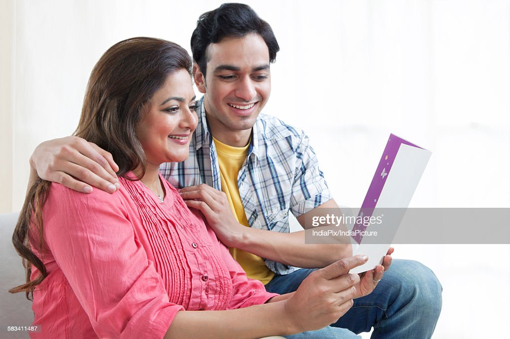 Mother reading card with son : Stock Photo