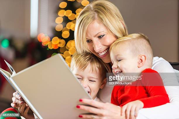 Mother reading Christmas bedtime story to happy young sons