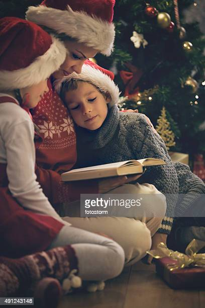 Mother reading Christmas stories to children
