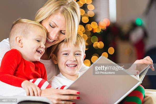 Mother reading Christmas story to happy little boys