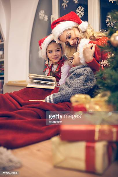 Mother reading Christmas story to her children