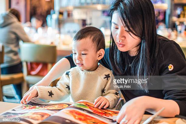 Mother reading menu to baby boy in restaurant