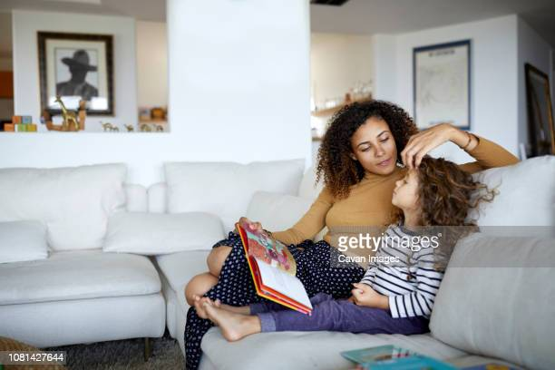 mother reading picture book for cute daughter while sitting on sofa at home - één ouder stockfoto's en -beelden