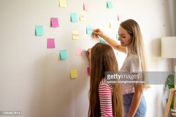 mother reading post it notes written by her daughter pasted on the wall of the room - thanks quotes stock pictures, royalty-free photos & images