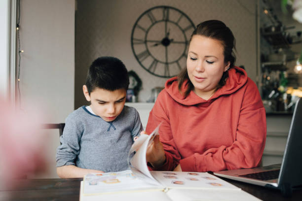 mother reading story from picture book for autistic son while sitting at home - handicap mental photos et images de collection