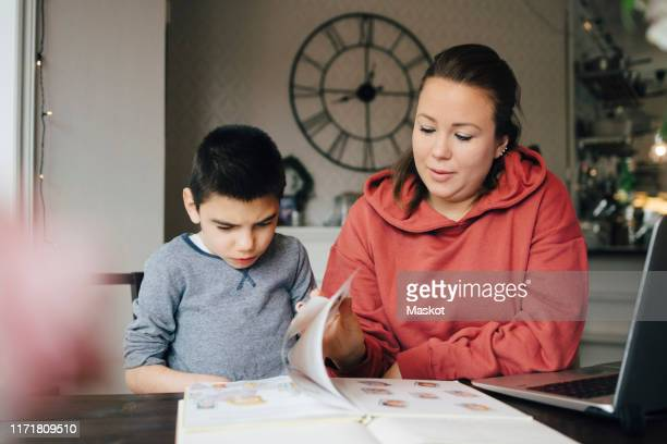 mother reading story from picture book for autistic son while sitting at home - 自閉症 ストックフォトと画像